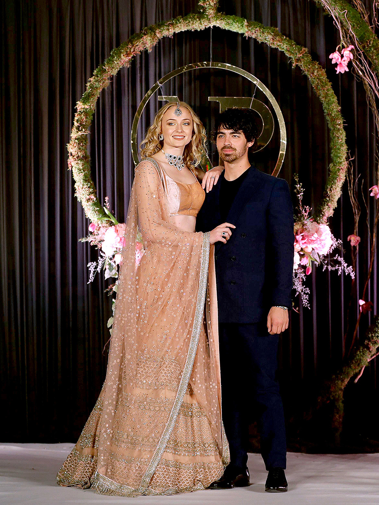 Mandatory Credit: Photo by Altaf Qadri/AP/REX/Shutterstock (10013599o) Joe Jonas, Sophie Turner. Joe Jonas and his fiancé and Game of Thrones actress Sophie Turner pose for photographs during the wedding reception of Bollywood actress Priyanka Chopra and musician Nick Jonas in New Delhi, India Chopra Jonas Wedding, New Delhi, India - 04 Dec 2018